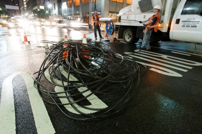 Workers install fiber optic cables under the streets of the Manhattan.