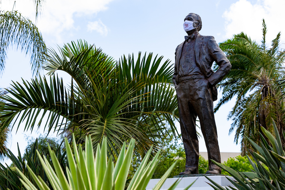 Statue of Jerome P. Keuper, Florida Tech founder, wearing a white face covering with Florida Tech logo on it