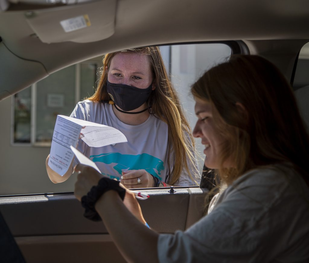 Student Elizabeth Christ fills out forms while in the car while volunteer Natalie Holliday waits for the form.