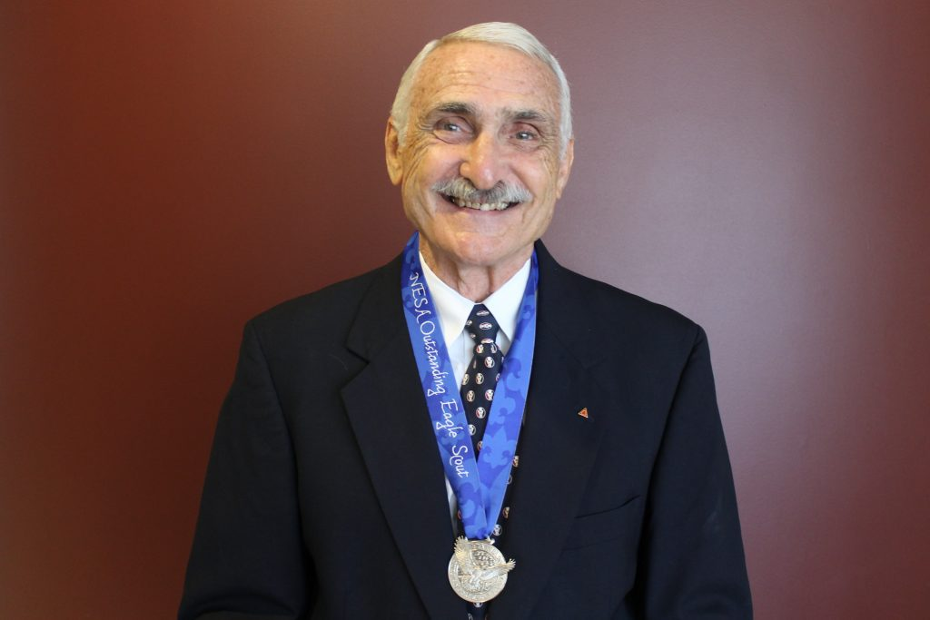 George Maul smiling at camera with ational Eagle Scout Association Outstanding Eagle Scout Award medal around his neck