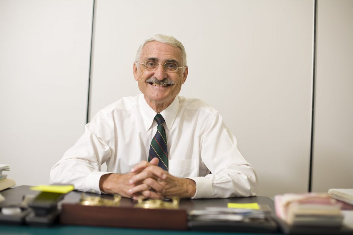 George Maul, retired professor and former department of marine and environmental systems head, sits at a desk smiling at the camera