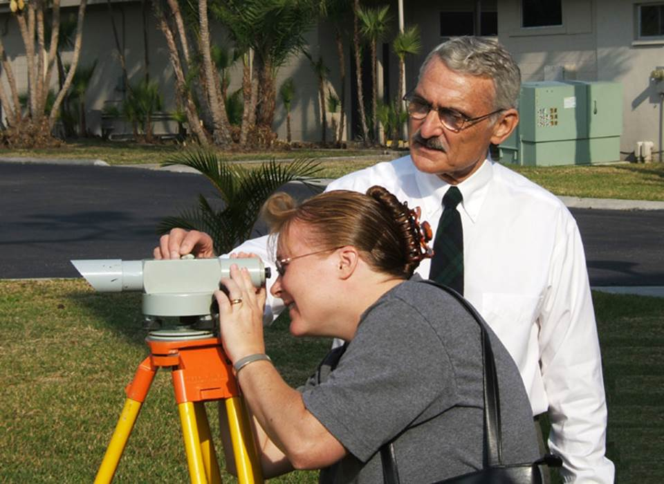 George Maul training a student in surveying, one of his favorite professional activities