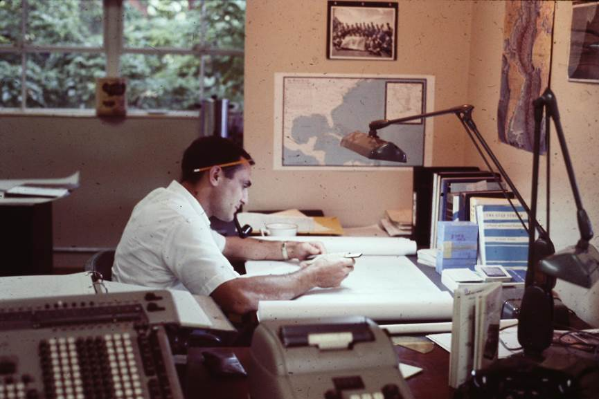 George Maul sits at a desk with a large paper in front of him and pencil behind his ear