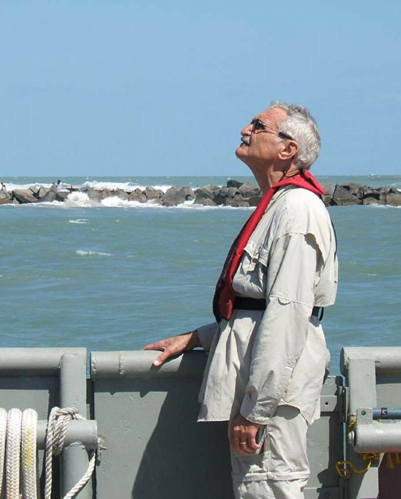 George Maul looking up into the sky with the ocean and a wall of rocks in the background