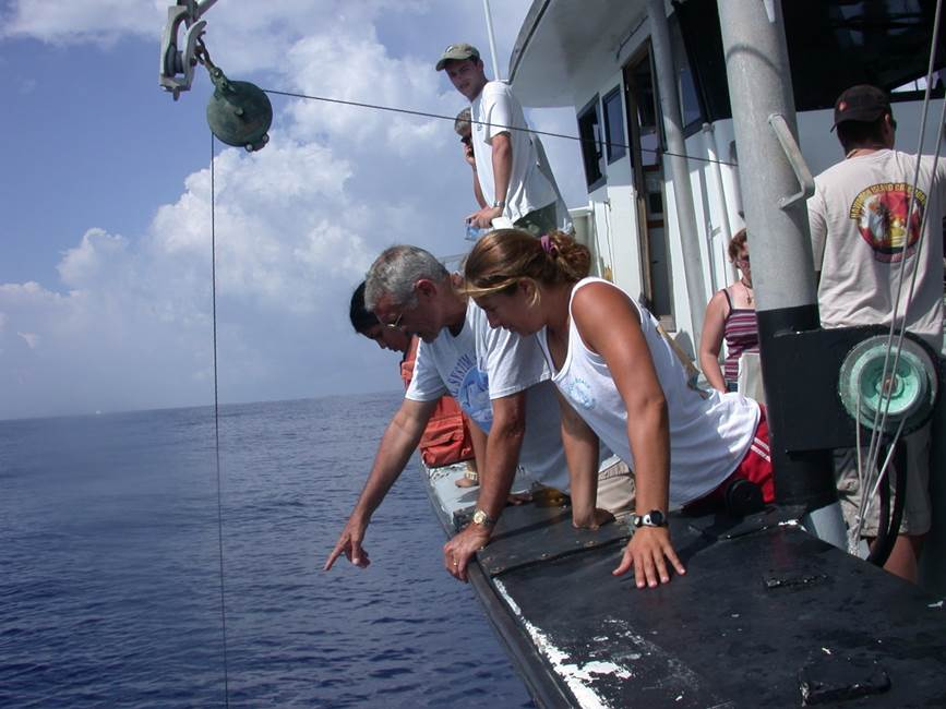 Professor pointing out something in the water to two students on a water vessel.