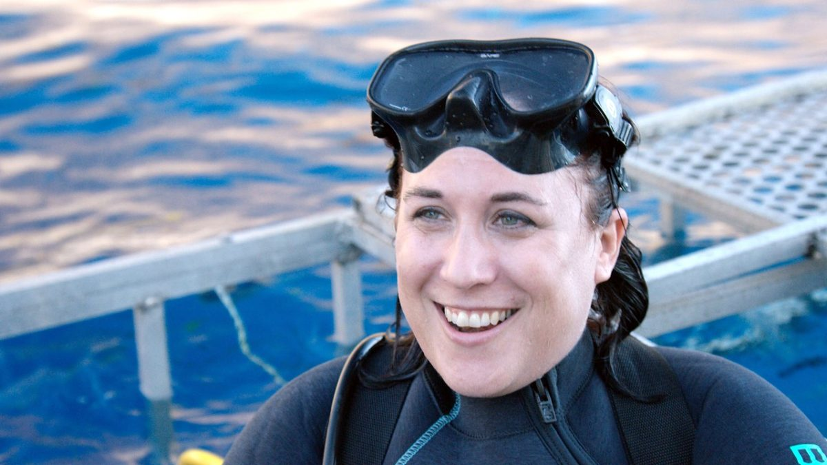 Toby Daly-Engel in wetsuit near shark cage.