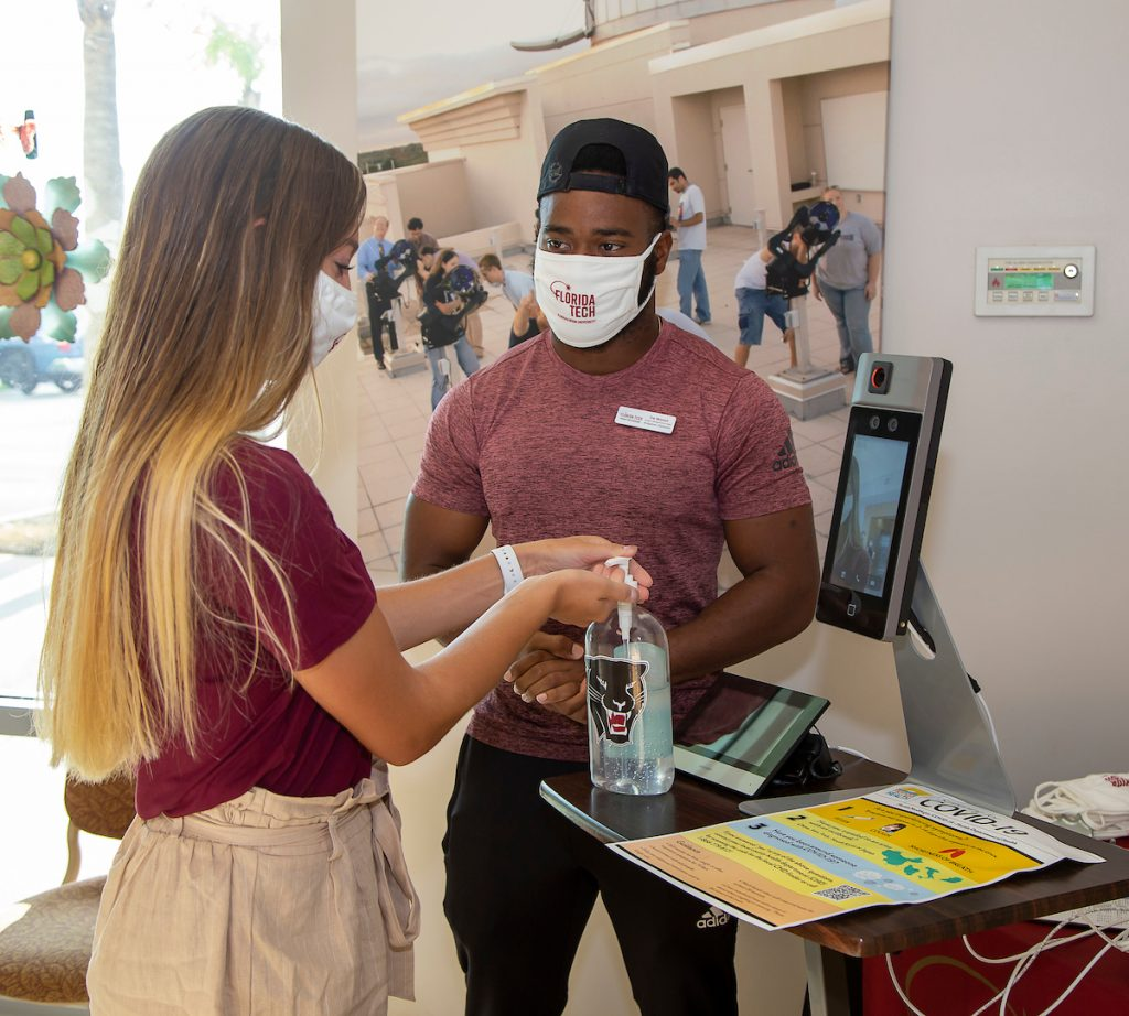 Students wearing face masks undergo campus COVID-19 screening with temperature checks and hand sanitizer