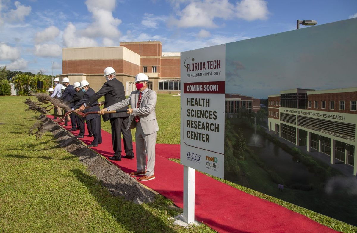 participants shoveling dirt at groundbreaking for Health Sciences Research Center
