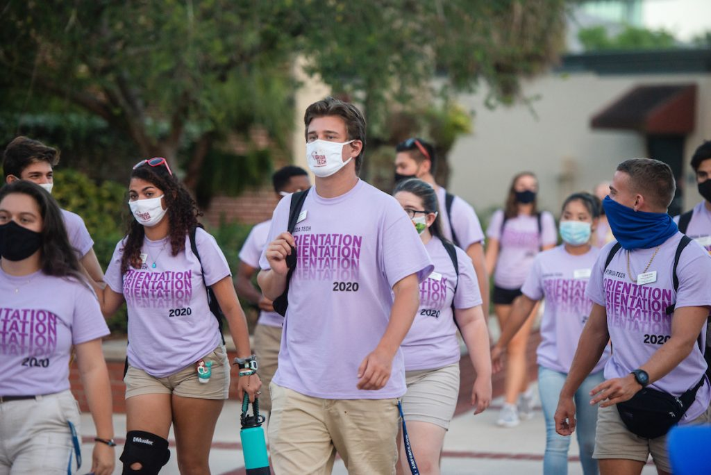 "Group of students wearing ""Orientation 2020"" t-shirts and face masks on campus"