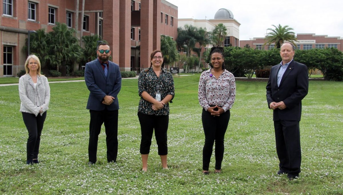 Image shows College of Psychology and Liberal Arts Dean Lisa Steelman, assistant professor of clinical psychology Patrick Aragon, students Shelby Gregson and Tenasia Wynn, and Joel Thomas, president of the Winter Haven Hospital Foundation standing on the Olin Quad.