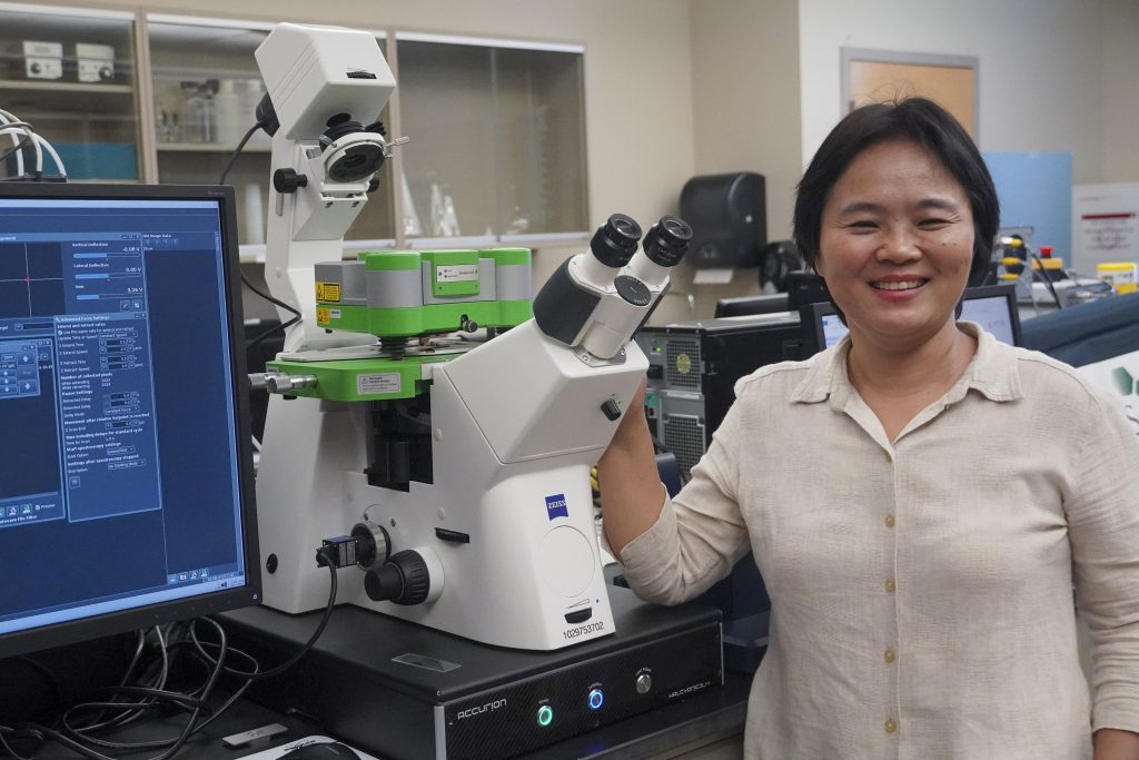 Linxia Gu, biomedical and chemical engineering and sciences and mechanical and civil engineering professor, with the university's new atomic force microscope housed in her Bio-Mechanics Laboratory