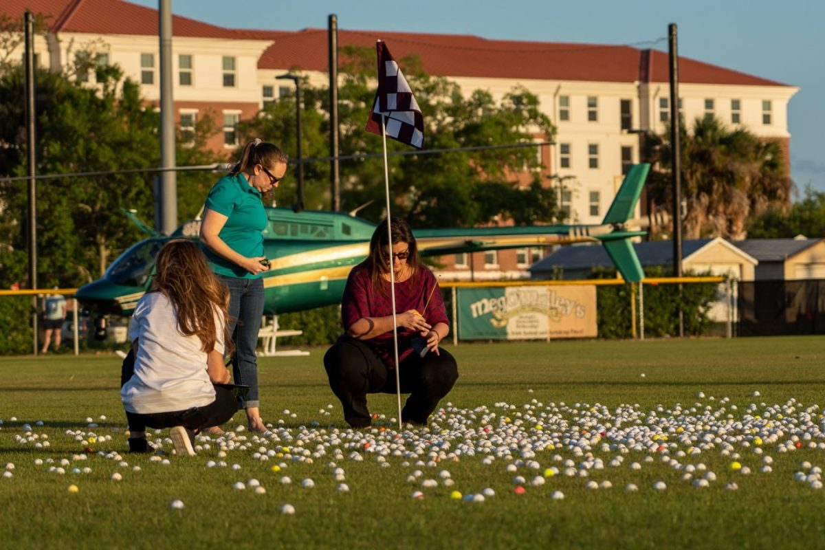 Three people work to measure the golf ball distances from the pin.