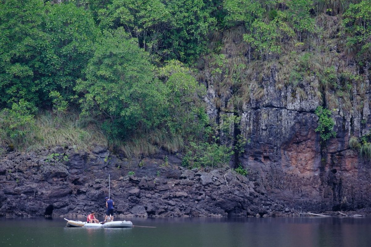 A raft floats on a large lake next to a steep rock wall in Brazil.