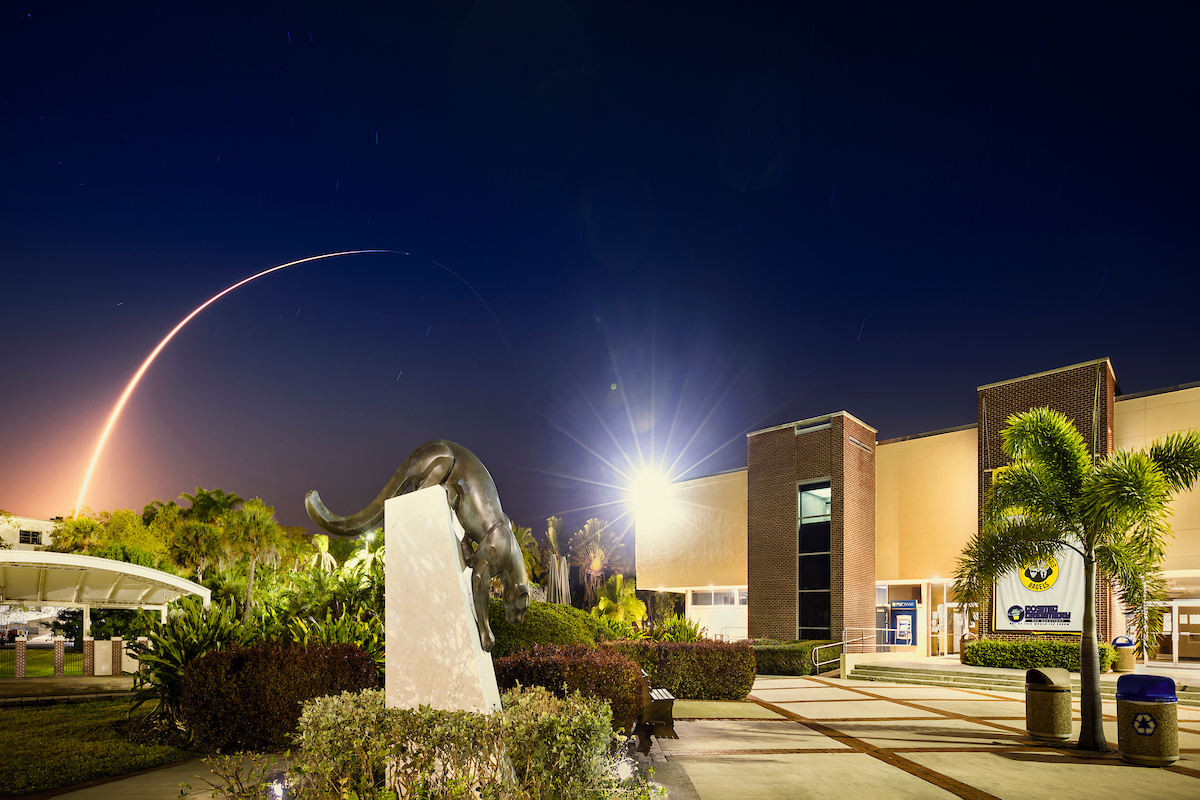 Night sky lit up by a launch over Panther statue in Panther Plaza.