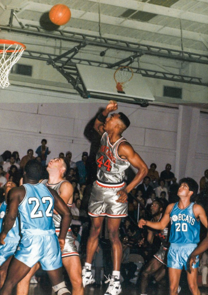 Man shooting a basketball in the air in front of a crowd and among 4 other players