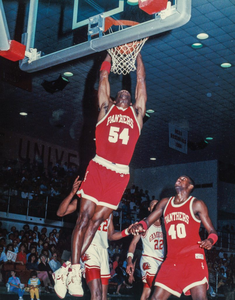 Man dunking a basketball in front of a crowd and among three other players
