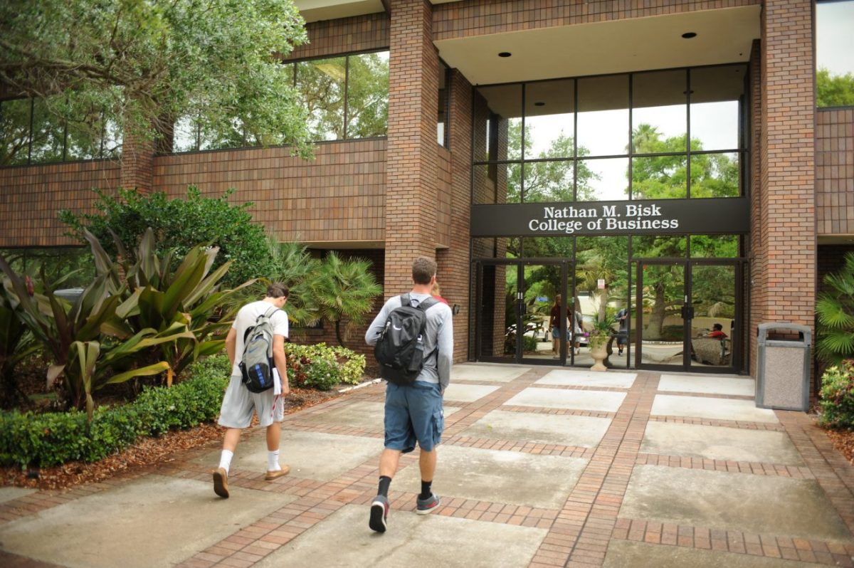 An exterior image of Bisk College of entry to the Bisk College of Business, with two stuedents walking toward the doorway.