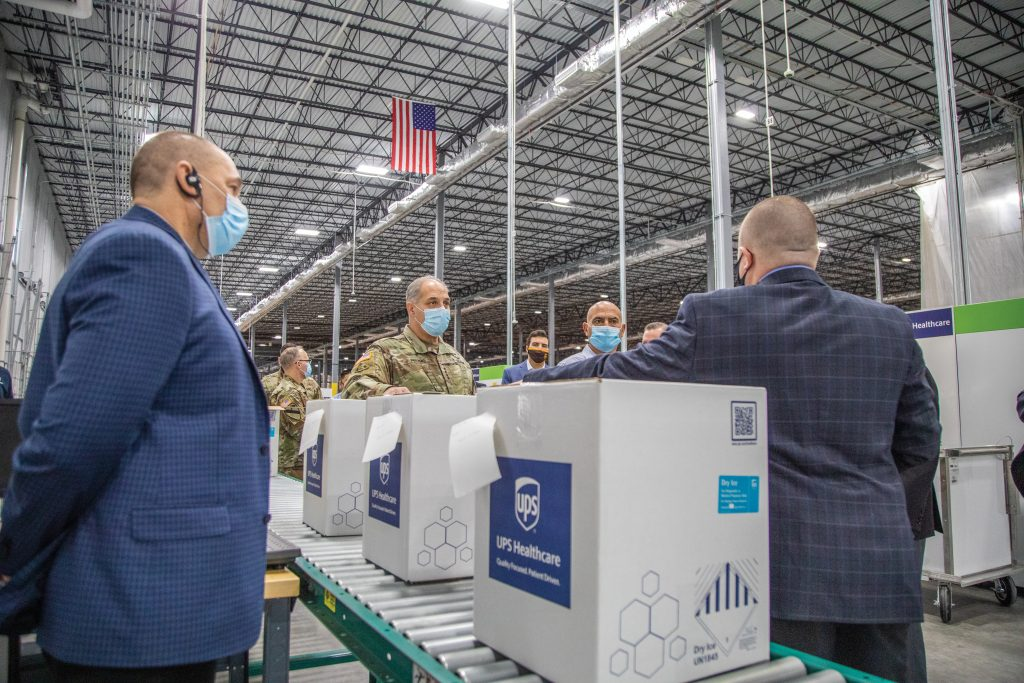 Two men in suits and some in military uniforms in a large warehouse with boxes of vaccines