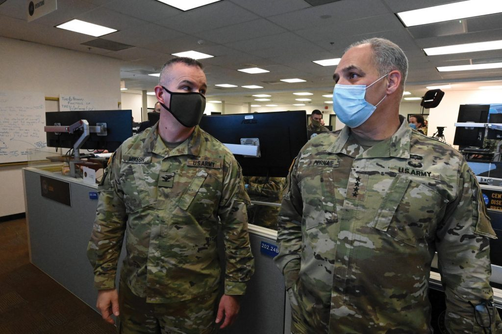 Two men in military uniforms and face masks in an office