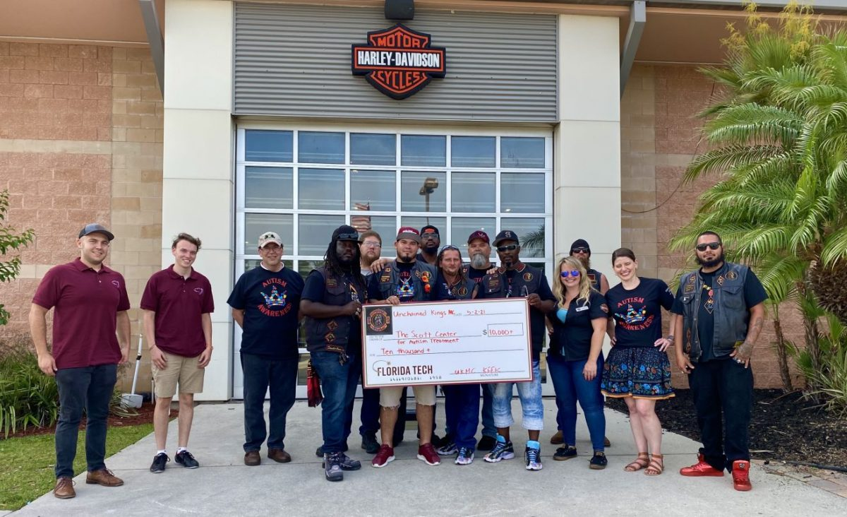 Members of the Unchained Kings motorcycle club pose with a large check representing the group's donation to the Scott Center for Autism Treatment.