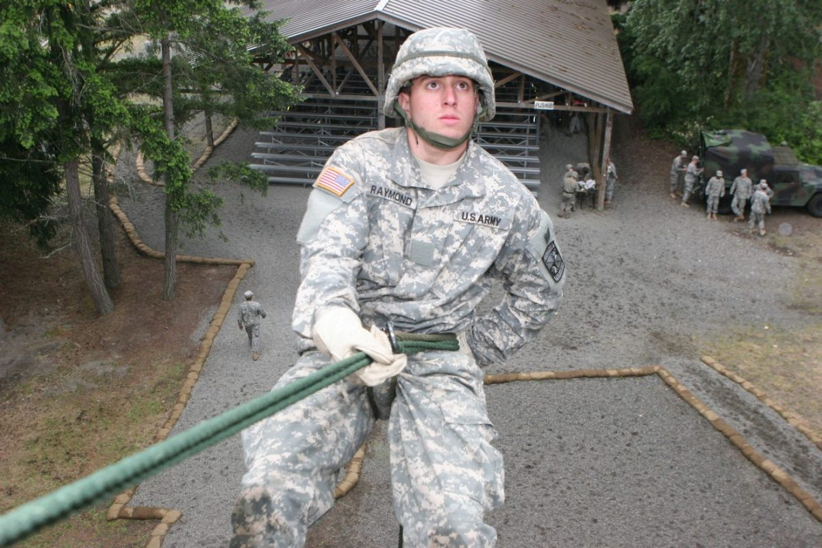 an ROTC student in camo repelling down a wall