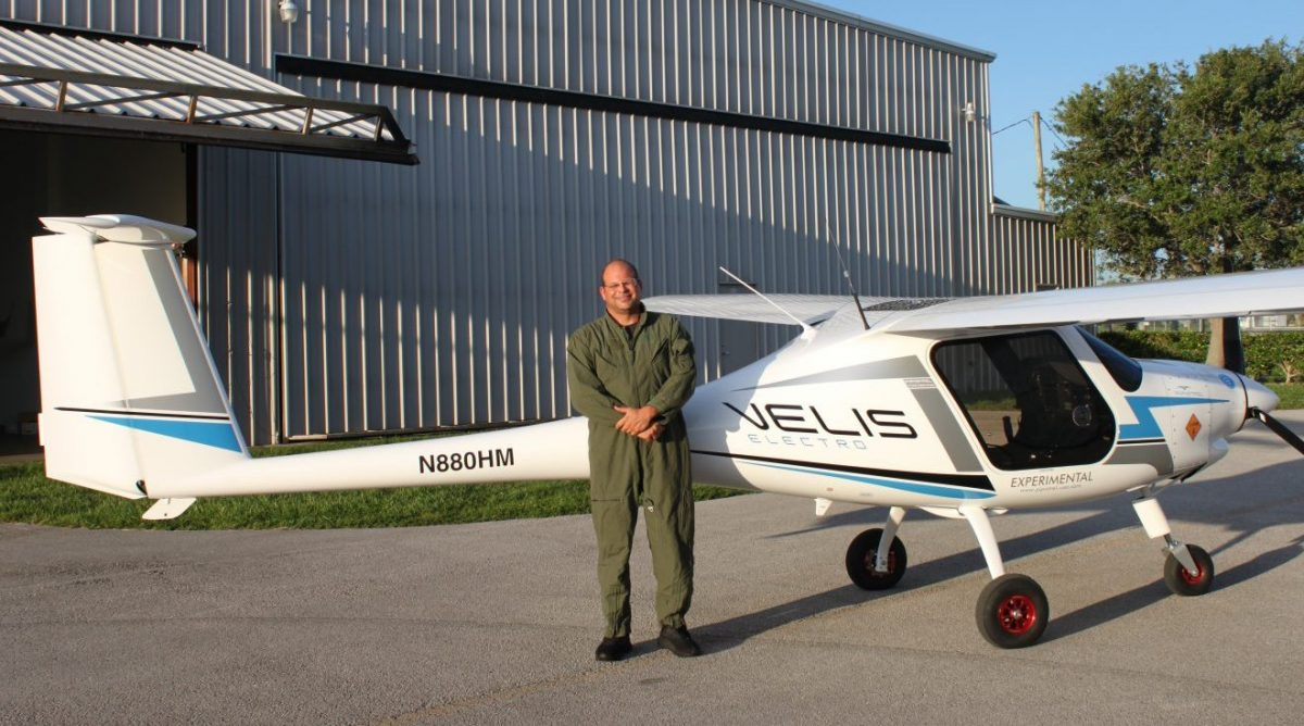 Pilot Isaac Silver, wearing a green flight jumpsuit, stands in front of the Pipistrel Velis Electro electric airplane.