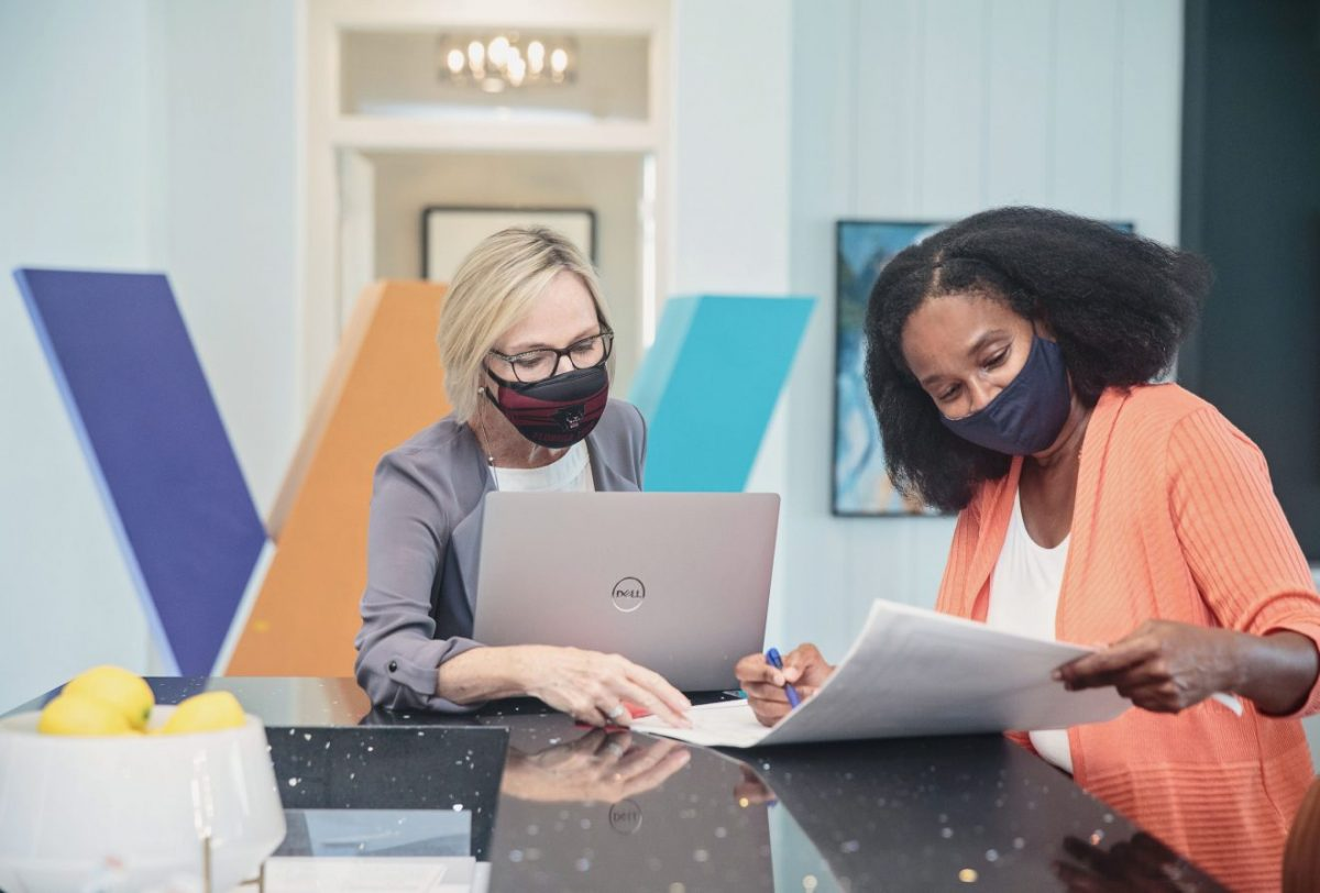 Two women -- one a weVENTURE employee, the other a client -- work together with paperwork and a laptop at a high table in an office setting.