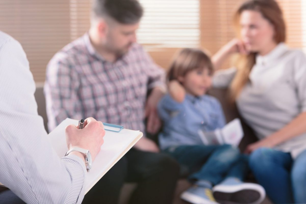 A family, blurred in the picture, sits on a coach as a person with a clipboard, likely a therapist, sits nearby.