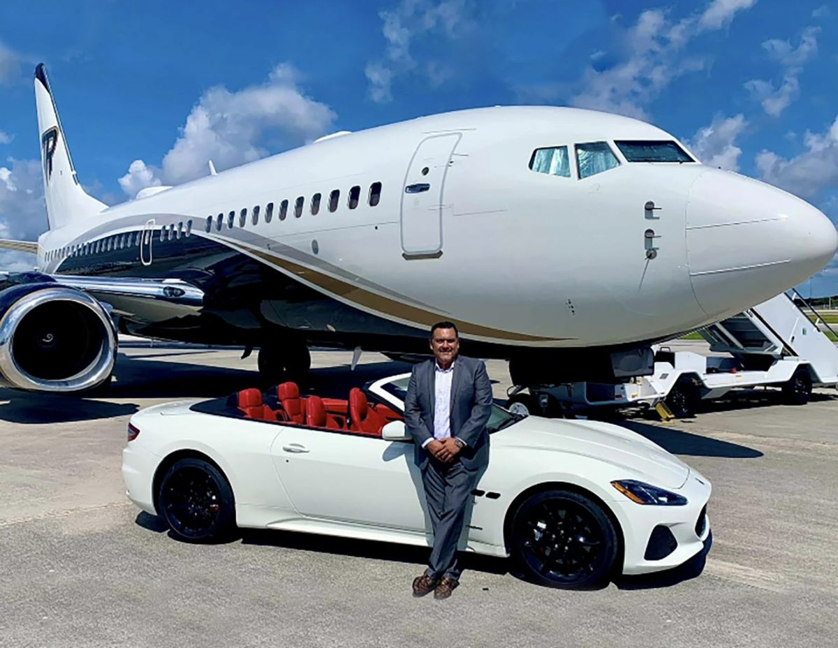 Man standing next to car and vehicle.