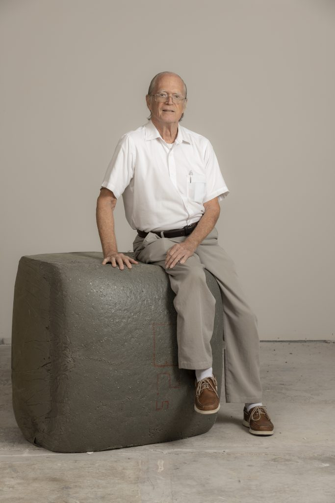 Florida Tech professor Gordon Nelson sits on a block of the flame-resistant foam he has helped develop over this career.