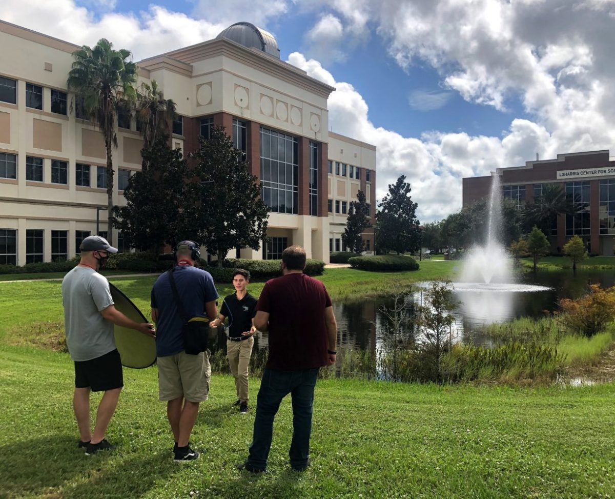 Student Giulio Cristello stands on grass near academic buildings as a three-person film crew records an interview.